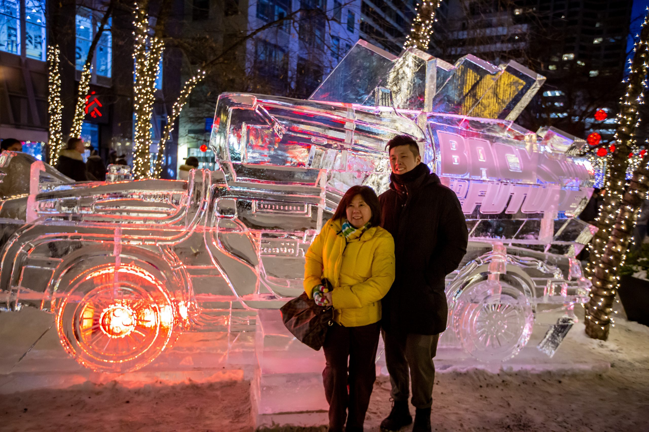 Couple pose in front of a DeLorean at Icefest 2020