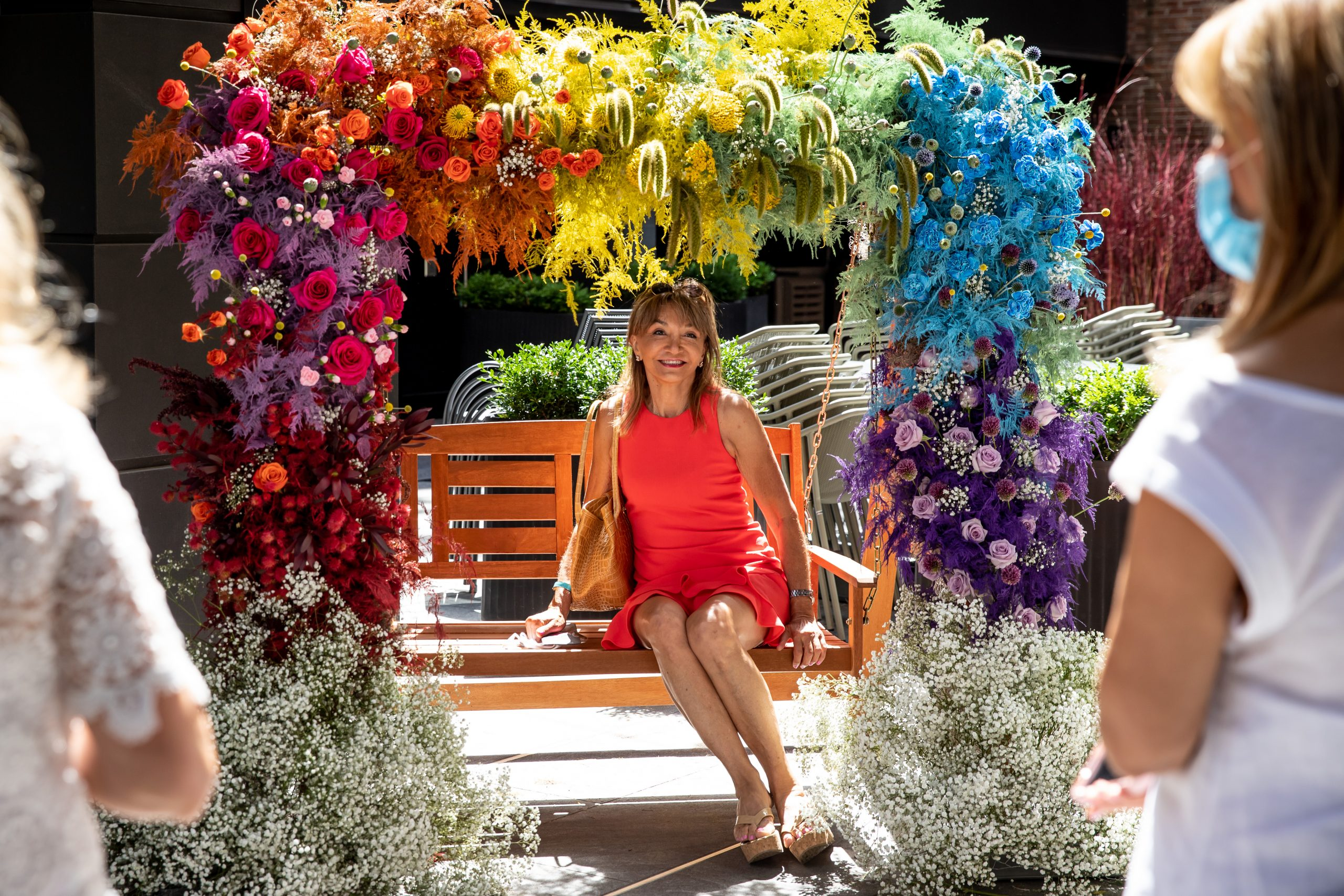A swing decorated in bright coloured flowers